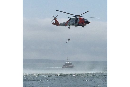 U.S. Coast Guard helicopter recovers a swimmer during a search and rescue demonstration in Woods Hole Harbor