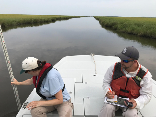 Dawn Davis (Habitat Conservation Division) measuring water depth and Jason Kroll (NOAA Restoration Center) recording the GPS coordinates at the West Louisiana Highway One Marsh Creation project site visit..jpg