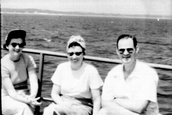 Sitting on deck, 2 women and 1 man.