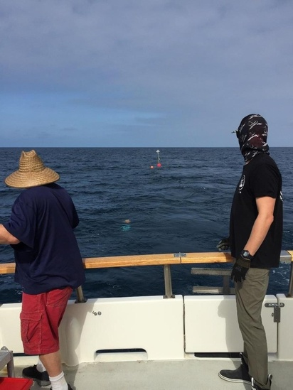Crew members looking off the stern of the M/V Horizon at the drifting buoy they just deployed in the ocean. The high flyer and float from the drifting buoy can be seen floating in the distance.