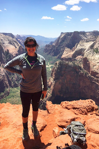 Kiersten Curti at the top of the Observation Point Trail overlooking a canyon.