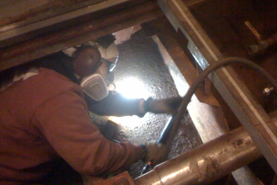 Worker in protective gear and face mask working in the bilge.