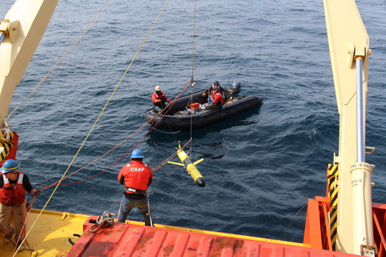 Several data collector personnel deploy a glider off the ship using ropes.