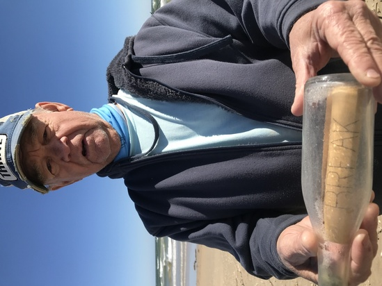 "Beachgoer Jim Duke with a ""science"" bottle he and wife Candy found along the shore"