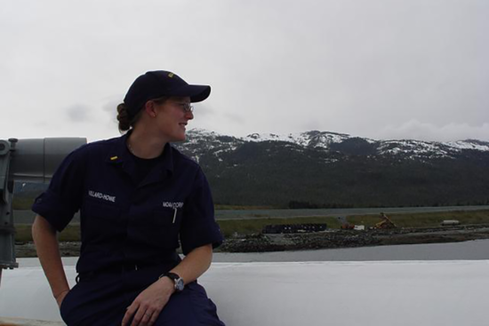 Female officer looking out at the Alaskan shore line.