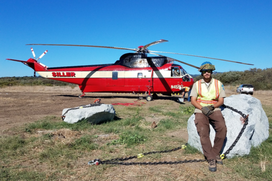 Fish Migration Vet Corps participant Ryan Sharrow in front of a helicopter.