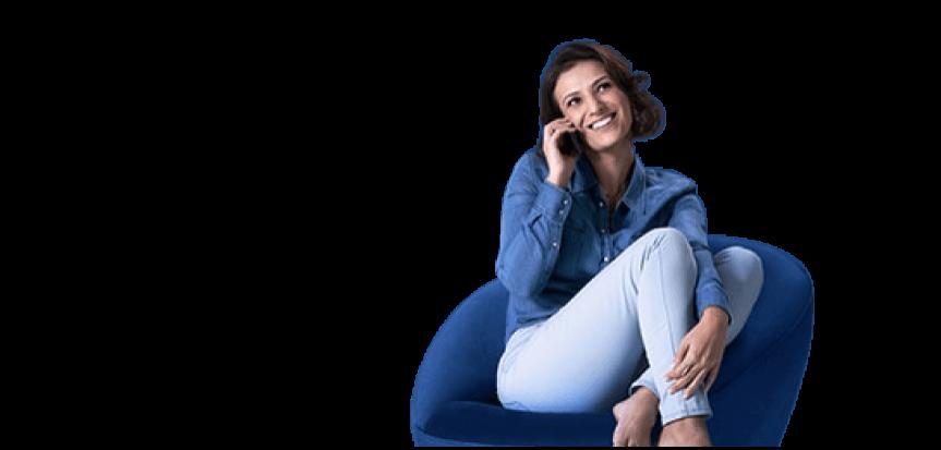 Mulher sentada em poltrona azul sorrindo enquanto fala ao telefone fixo